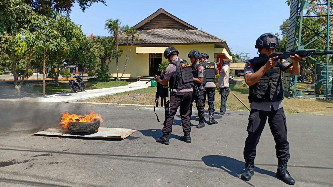 Tim Anti Anarkis Detasemen B Pelopor Brimob Polda Jatim memadamkan api akibat bom molotov.