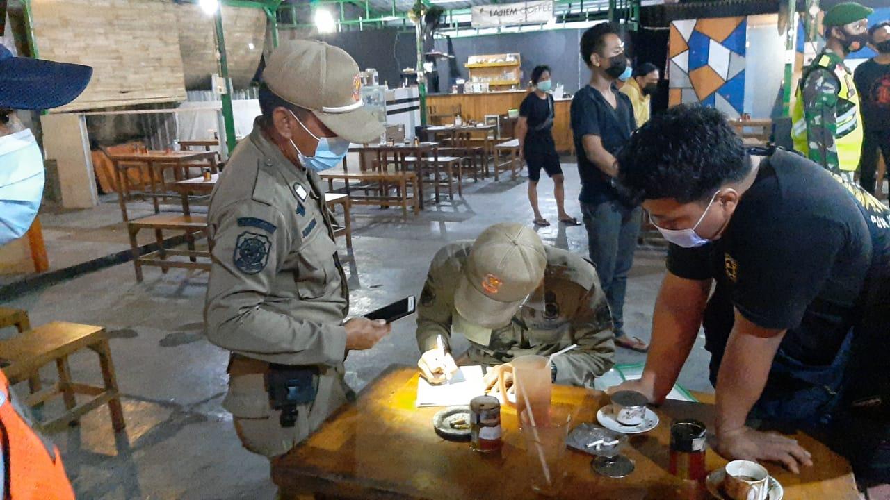 Petugas mendata warga yang tidak patuh terhadap prokes sebagai pencegahan Covid-19.