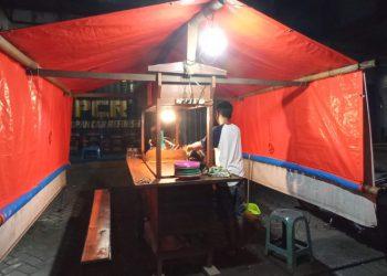 Anton saat menutup angkringannya pada masa PPKM di Kota Malang. (Foto: J Krisna/Javasatu.com)